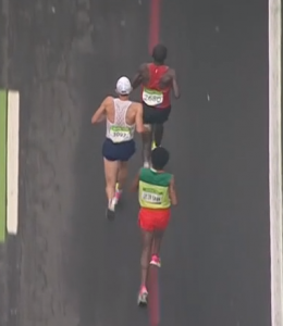 Notice Kipchoge and Lilesa turning upper bodies right, race numbers aligned with left legs. Rupp's number stays in the middle, as does the center of his upper back.