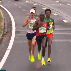 Notice Kipchoge and Lilesa's chests turned more than Rupp's. Rupp's shoulders are lifted. Also notice Lilesa prepared to land on the outside of his foot due to more rotation of thorax and pelvis.
